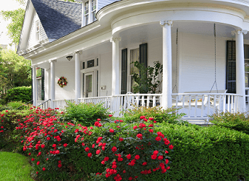 Nice older home with a wrap around porch and several well-maintained flower bushes and hedges in front