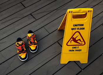 Pair of shoes next to a wet foor sign on the ground